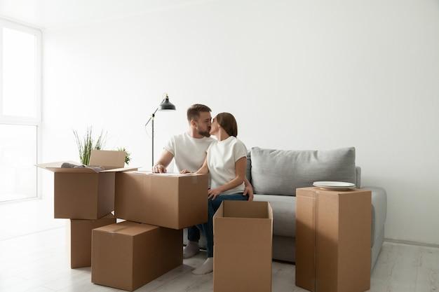 Пара целоваться, сидя на диване в гостиной с коробками