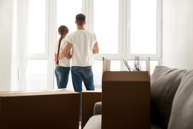 新しい家で未来を計画する窓を通して見るカップル