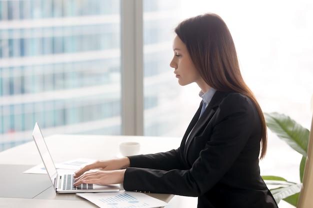 Успешная серьезная бизнес-леди работает на офисном столе, используя ноутбук