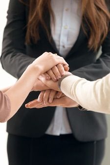 チーム管理の概念、手に参加するビジネス人々、垂直方向のクローズアップ
