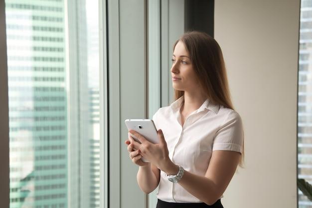 タブレットを押しながら窓を通して見る若い夢のような美しい女性実業家