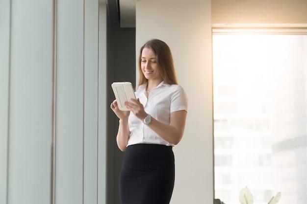 手でコンピューターのタブレットで立っている若い女性