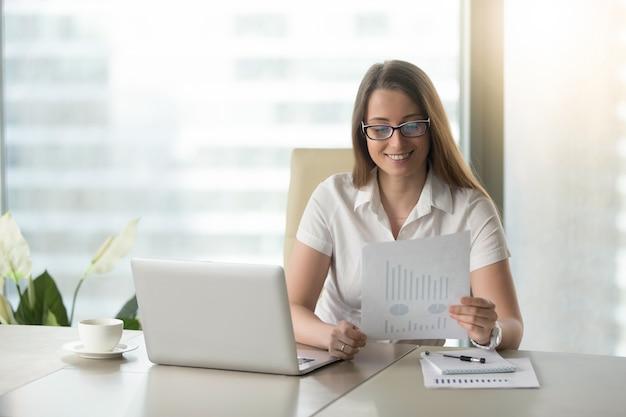 Довольная деловая женщина пересматривает финансовые результаты