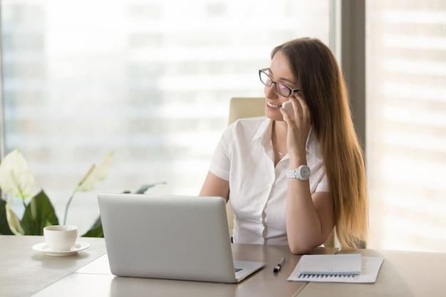 女性の財務顧問が電話でクライアントに相談します
