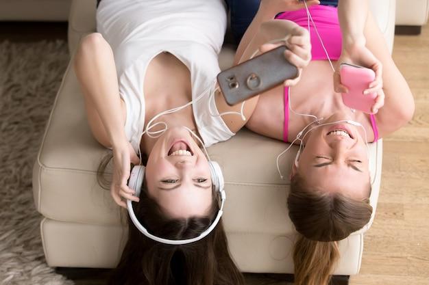 Возбужденные подруги наслаждаются музыкой в наушниках