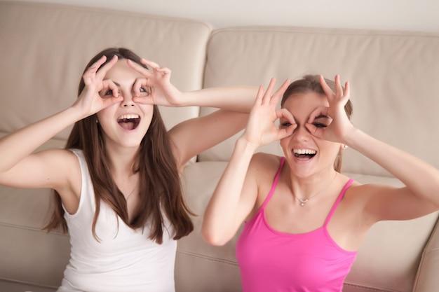 Две подружки глупо делают очки с пальцами.