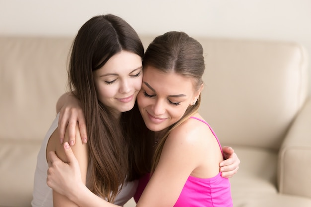 Две молодые женщины друзья нежно обнимаются на диване