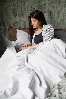 深刻な女性が午前中にベッドの上のニュースをオンラインでチェック