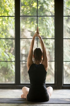 Молодая спортивная женщина в позе сукхасана, фон окна