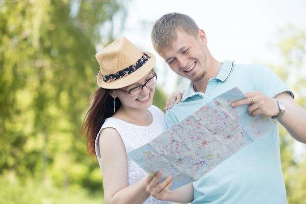 地図で楽しい時間を持つ若いカップル