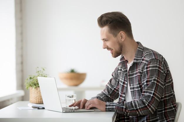笑みを浮かべて男フリーランサーのソフトウェアを使用してオンライン通信のラップトップに取り組んで
