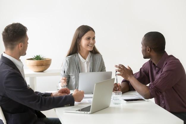 オフィスの会議で議論を持つ創造的な千年の多民族ビジネスチーム