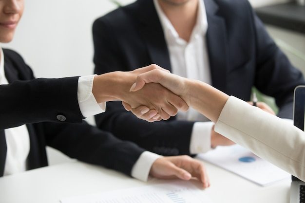 Женские руки тряску на групповой встрече, делая партнерство сделку, крупным планом
