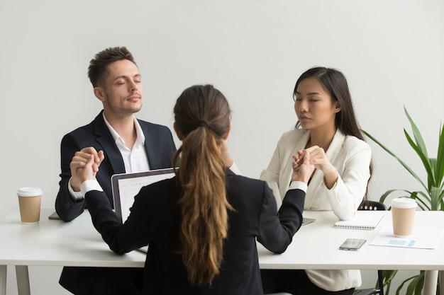 成功のための祈りを瞑想の手を繋いでいる気配りのある多様なチームの人々