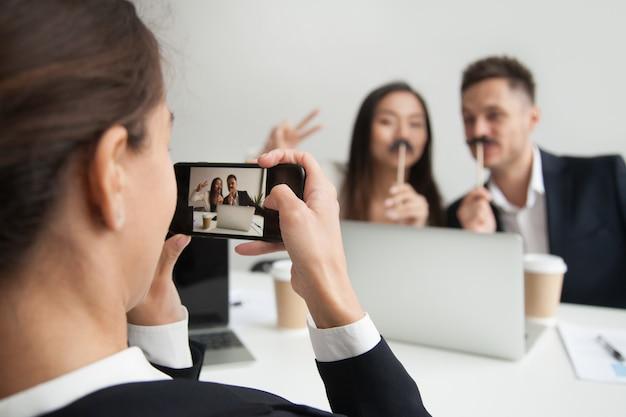 口ひげのアクセサリーをしようとしている同僚の写真を作る労働者