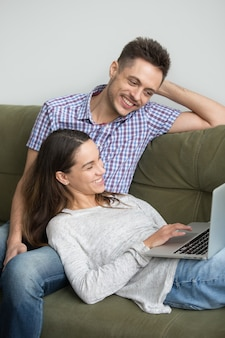 幸せなカップルのラップトップで一緒にビデオを見て