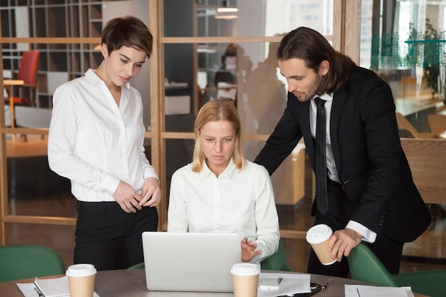 オフィスで一緒にオンラインのタスクを議論する深刻な集中ビジネスチーム