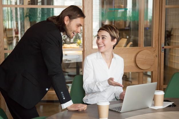 幸せなビジネスマンやビジネスウーマンのラップトップでオンラインで良いニュースを議論します。