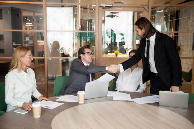 Генеральный директор пожимает руку работнику мужского пола, поздравляющему с продвижением по службе