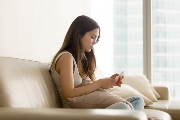 ソファーに座りながら電話を使用して悲しい十代の少女