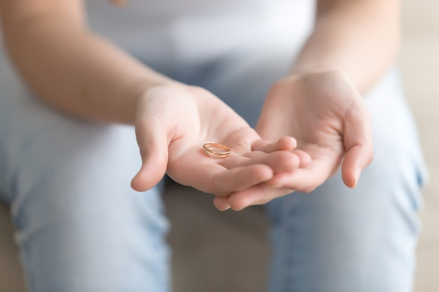 Крупным планом изображение золотого кольца в руках женщины