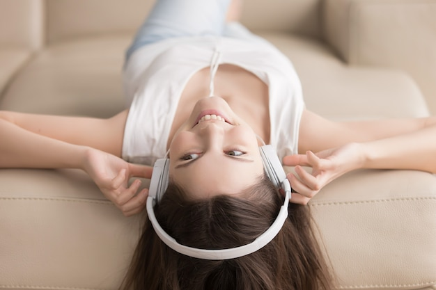 頭の上にヘッドフォンでソファーに横になっている若い女性