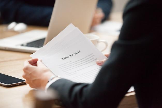 Концепция маркетингового плана чтения, коммерсантка держа документ, конец вверх по взгляду