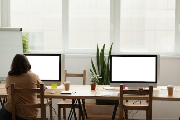 コンピューターで一人で働く女性と近代的なオフィスのコワーキングスペース