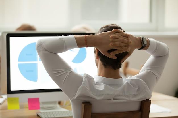 Вид сзади на бизнесмена, анализируя статистический отчет на экране компьютера