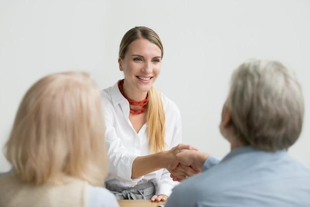 Улыбающаяся деловая женщина пожимает руку старшему человеку на собеседовании
