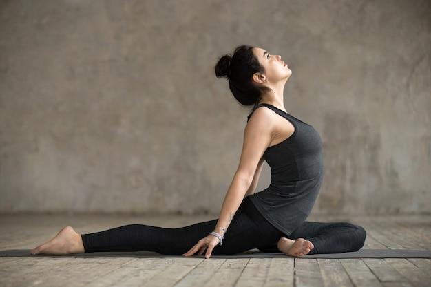 Молодая женщина делает упражнения одного голубя