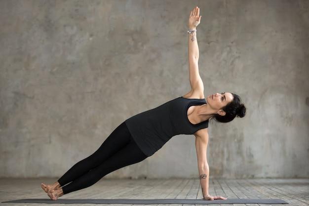 Молодая женщина делает упражнения васиштхасана