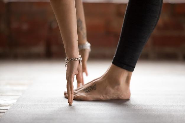 Молодая женщина делает упражнение уттанасана, вид сбоку