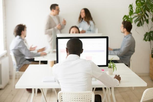 アフリカの従業員、多民族のオフィス、背面図のコンピューターで作業