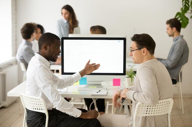 オフィスで一緒に議論ブレーンストーミングプロジェクトを持つ深刻な多民族の同僚