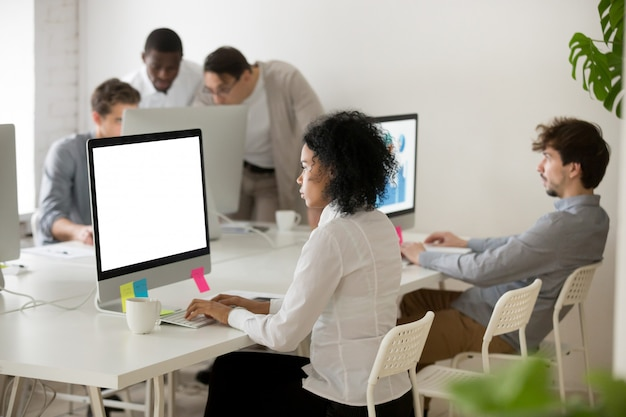 Афро-американская женщина-менеджер сосредоточилась на работе за компьютером в многонациональном офисе