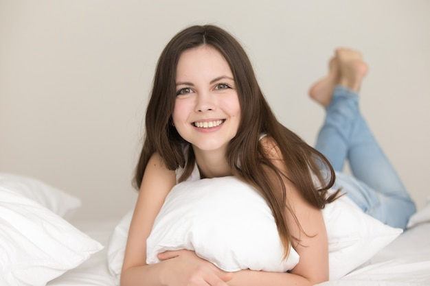 カメラで見ているベッドのきれいな女性の肖像画