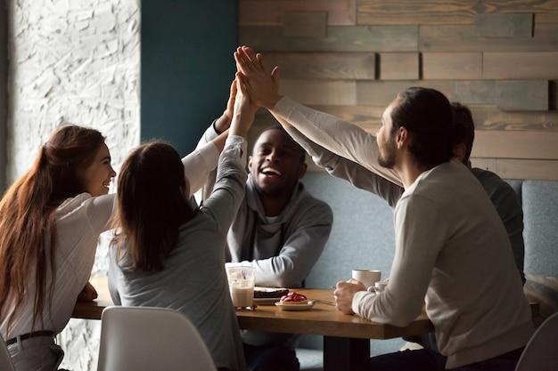 カフェミーティングで一緒にハイタッチを与える多様な親友が興奮