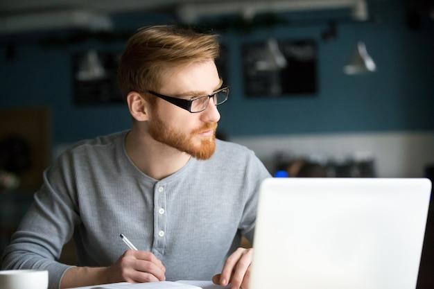 Вдумчивый человек, думая о новой идеи, написание заметок в кафе