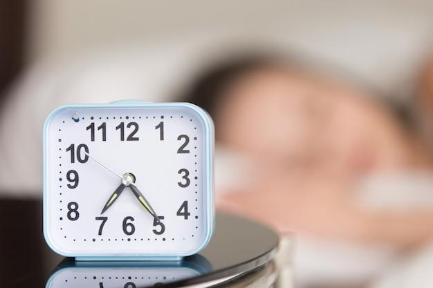 ベッドサイドテーブルの上の目覚まし時計の画像を閉じる