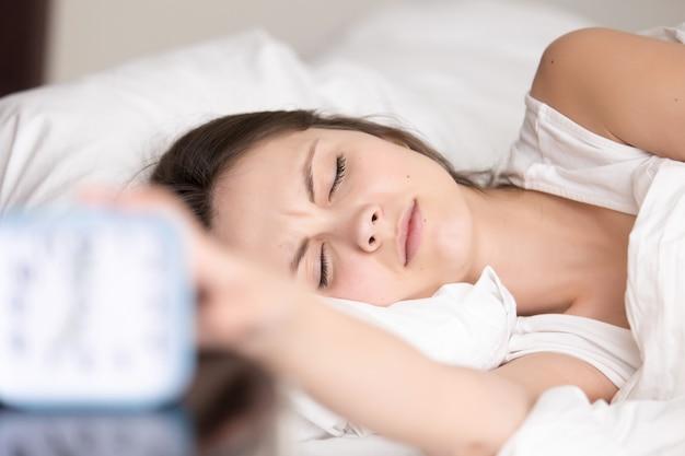 眠そうな若い女性が目覚まし時計の信号を消す