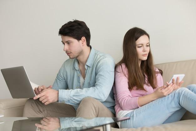 Молодая пара сидит спиной к спине, используя портативный компьютер