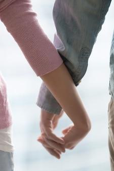 手を繋いでいる若いカップルのクローズアップ
