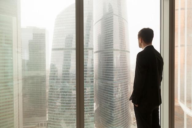 会社の役員が事務所の窓から見る