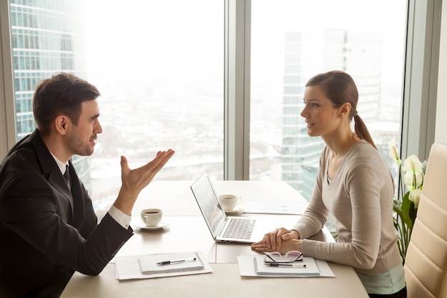ビジネスマンやビジネスウーマンのオフィスの机で仕事を議論します。