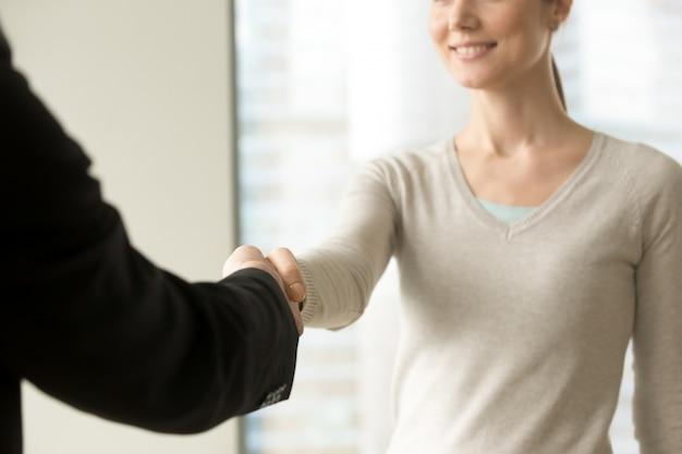 Улыбающаяся деловая женщина пожимает руку бизнесмену в офисе