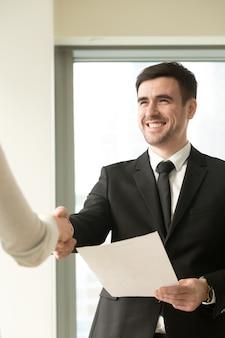 Счастливый улыбающийся бизнесмен в костюме, пожимая женскую руку