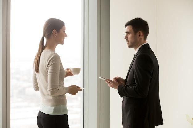 ビジネスチームのメンバーがオフィスで話しているの笑みを浮かべてください。