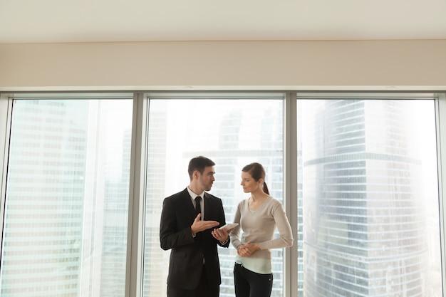 Улыбающиеся коллеги обсуждают бизнес-проект
