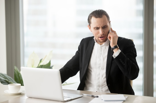 携帯電話で話している怒っているビジネスマン